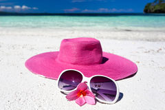 Pink summer hat on beach with sunglasses and plumeria. Pink panama on tropical beach, nobody. Vacation concept Stock Photos