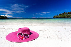 Pink summer hat on beach with sunglasses and plumeria. Pink panama on tropical beach, nobody. Vacation concept Stock Photography