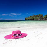 Pink summer hat on beach with sunglasses and plumeria. Pink panama on tropical beach, nobody. Vacation concept Stock Image