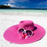 Pink summer hat on beach with sunglasses and plumeria. Pink panama on tropical beach, nobody. Vacation concept Royalty Free Stock Photography