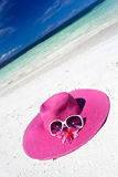 Pink summer hat on beach with sunglasses and plumeria. Pink panama on tropical beach, nobody. Vacation concept Royalty Free Stock Images