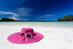 Pink summer hat on beach with sunglasses and plumeria. Pink panama on tropical beach, nobody. Vacation concept Stock Images