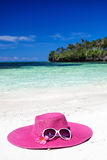 Pink summer hat on beach with sunglasses and plumeria. Pink panama on tropical beach, nobody. Vacation concept Royalty Free Stock Image