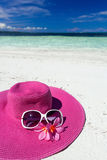 Pink summer hat on beach with sunglasses and plumeria Royalty Free Stock Images