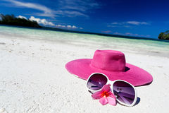 Pink summer hat on beach with sunglasses and plumeria. Pink panama on tropical beach, nobody. Vacation concept Royalty Free Stock Photos