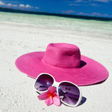 Pink summer hat on beach with sunglasses and plumeria Stock Image