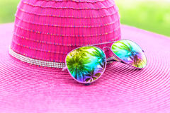 Pink summer hat and colorful sunglasses with palm tree reflectio Royalty Free Stock Photos