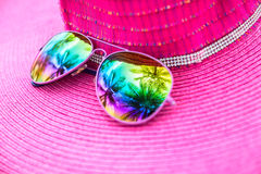 Pink summer hat and colorful sunglasses with palm tree reflectio Royalty Free Stock Photography