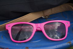 Pink sunglasses reflecting a cloudy sky Royalty Free Stock Image