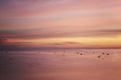 Pink sunrise over the sea. Dawn sky over the sea, crossed by yellow, pink and orange stripes Stock Image