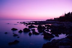 Pink Sunset. Fantastic scene of pink sky reflection at rocky bay royalty free stock images