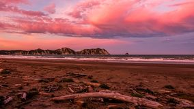 Pink sunset at the beach near Waikaremoana New Zealand. Sunset with pink clouds, view to the ocean from the beach royalty free stock images