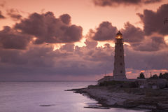 Pink sunset with clouds behind the old lighthouse Stock Image