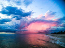 Pink sunset clouds over beach. A bright, vibrant pink cloud over Naples Florida surf Royalty Free Stock Photo