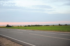 Pink sunset on an empty road with markings. Country landscape. Atmosphere of travel Stock Image