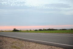 Pink sunset on an empty road with markings. Country landscape. Atmosphere of travel Stock Photo