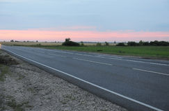 Pink sunset on an empty road with markings. Country landscape. Atmosphere of travel Royalty Free Stock Image