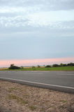 Pink sunset on an empty road with markings. Country landscape. Atmosphere of travel Stock Photography