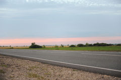 Pink sunset on an empty road with markings. Country landscape. Atmosphere of travel Royalty Free Stock Images