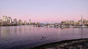 Pink sunset and full moon over boat marina. Royalty Free Stock Photos