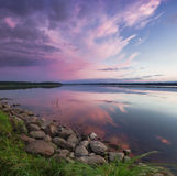 Pink sunset on the lake. Evening blue sky reflected in the water. Camping near the lake. Royalty Free Stock Photography