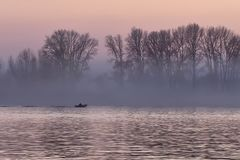 Pink sunset on the Ob River with a floating boat royalty free stock photography