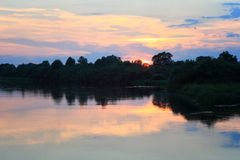 Pink sunset over river in summer stock photo