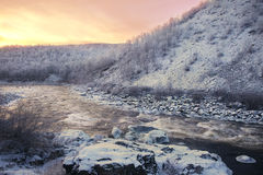 Pink sunset over winter mountain river. Sunset over winter river flowing through the mountains Royalty Free Stock Images