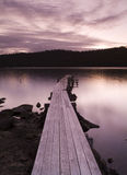 Pink Sunset Pier. Purple and pink sunset over water and jetty royalty free stock photos