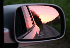Pink sunset in rear view mirror. Of car Stock Photos