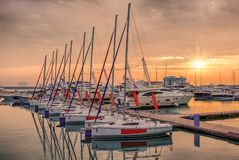 Pink sunset in the sea harbor with moored yachts stock photo
