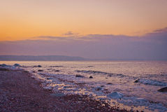 Pink sunset on the sea and the island in the distance Stock Photography