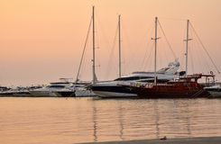 Pink sunset on the sea lights yachts. Sunshine silence boat stock photo