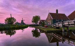 Pink sunset at the Zaanse Schans. Hazy clouds result in a soft sunset with pink and magenta tones, complimentary to the green in the buildings and trees stock image