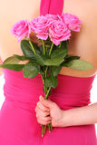Pink surprise. A picture of a young woman hiding a bunch of pink roses behind her back over white background Stock Image