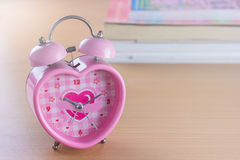 Pink sweet heart shape of clock on wooden background  . Stock Photos