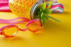 Pink swimming glasses for kids and pineapple mason jar for juice. Vacantion, summer, holidays concept. Copy space stock photography