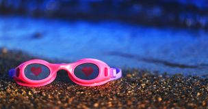 Pink swimming glasses on the sand with the red hearts on the len stock photos
