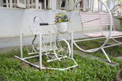 Pink swing and white small decorating bicycle. In the garden Royalty Free Stock Photo