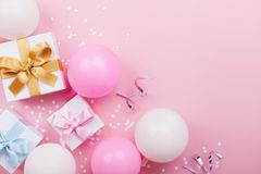Pink table with balloons, gift or present box and confetti top view. Flat lay. Composition for birthday or party theme.