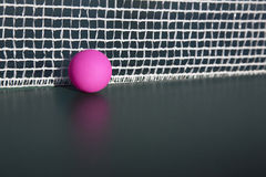 Pink table tennis ball  in the net. Pink table tennis table and detail of net Royalty Free Stock Photo