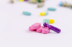 Pink tablets and violet capsules Stock Image