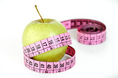 Pink tailoring meter and apple Royalty Free Stock Image