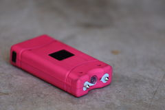 Pink Taser. A close up view of a pink taser laying on the ground Stock Photo