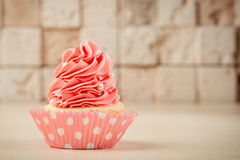 Pink tasty cupcake on table on brick wall background. stock photography