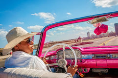 Pink taxi ride on Malecon in Old Havana, Cuba -March 2016. Cuban private taxi driver in traditional white hat driving a classic American car - a Fairlane 500 Stock Photography