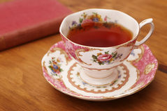 Pink Tea Cup and Antique Book Stock Image