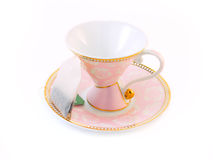 Pink tea cup on a saucer. And a tea bag Royalty Free Stock Photo
