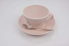 Pink teacup, pink platter. Pink teacup, pink on a plate with a spoon Royalty Free Stock Photos