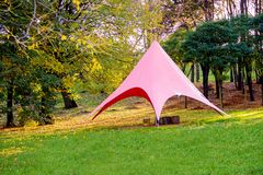 Pink tent in the woods on the green grass on a sunny day royalty free stock photos